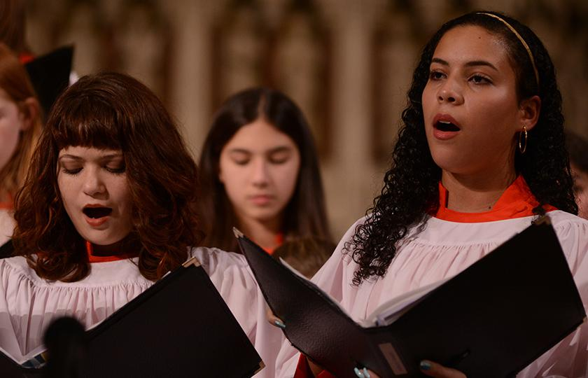 Trinity Youth Chorus members sing in white and red robes at Trinity Church