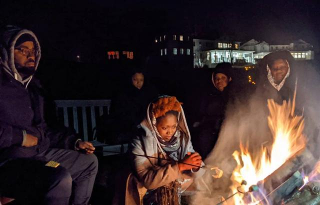 A group of adults, bundled up in coats and hoods, roasts s'mores