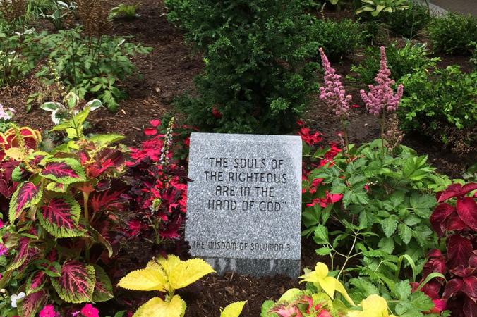"A stone garden marker engraved with a quote from Salomon 3:1, ""The souls of the righteous are in the hand of god."""