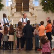 Children gather around the altar in St. Paul's Chapel