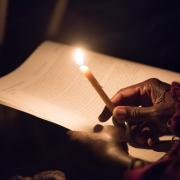 A person holds a candle to read the prayer.
