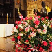 Bright pink flowers in front of the Trinity Church altar with the Lenten linen on it