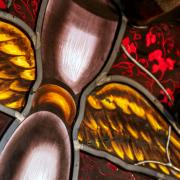 Stained glass image of an hourglass with wings