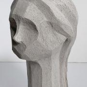 A gray slay sculpture of an abstract human bust