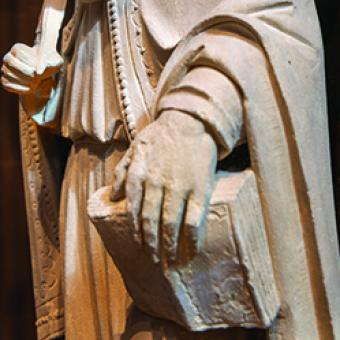 Detail of sculpture; hand holding book