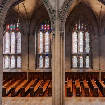 A wide shot of empty pews against a wall of stained glass windows in Trinity Church Wall Street