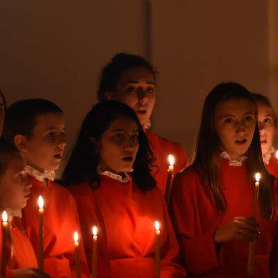 Trinity Youth Chorus members in red performing at Compline by Candlelight