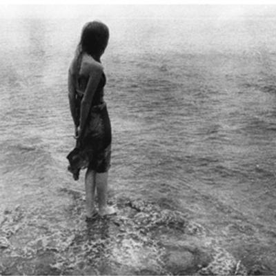 Woman standing on a shoreline, black and white