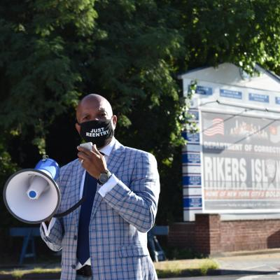 "A masked man speaks into a megaphone while standing in front of a sign that says ""Rikers Island."""