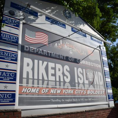 "A sign that reads, ""Department of Corrections: Rikers Island. Home of New York City's Boldest."""