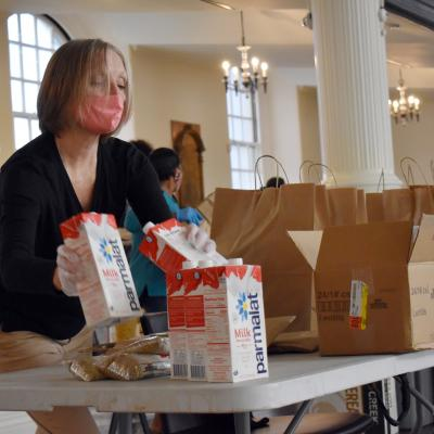 A masked woman packs boxes of milk into brown bags.