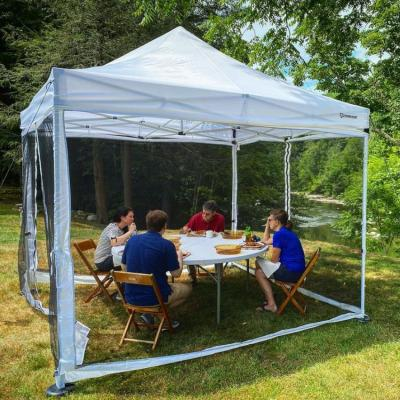 Four guests eat a socially-distanced lunch in a tent near the Housatonic River