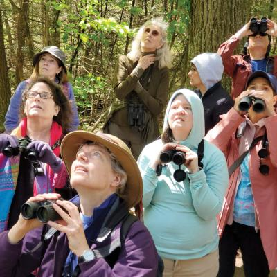 A group of adults uses binoculars to find birds during a retreat