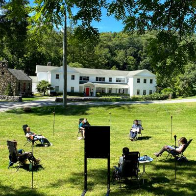 Socially-distanced group meets in a circle on the shaded green lawn of the Retreat Center