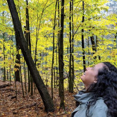 Woman smiling while looking up at trees during a hike