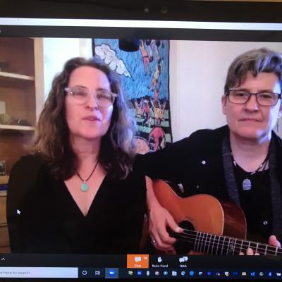 Two women singing, one playing a guitar