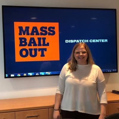 "A young woman stands in front of a screen, which reads ""Mass Bail Out Dispatch Center."""