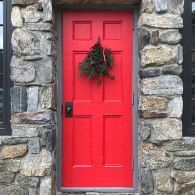 Red door on the side of the Chapel, decorated with Christmas greenery