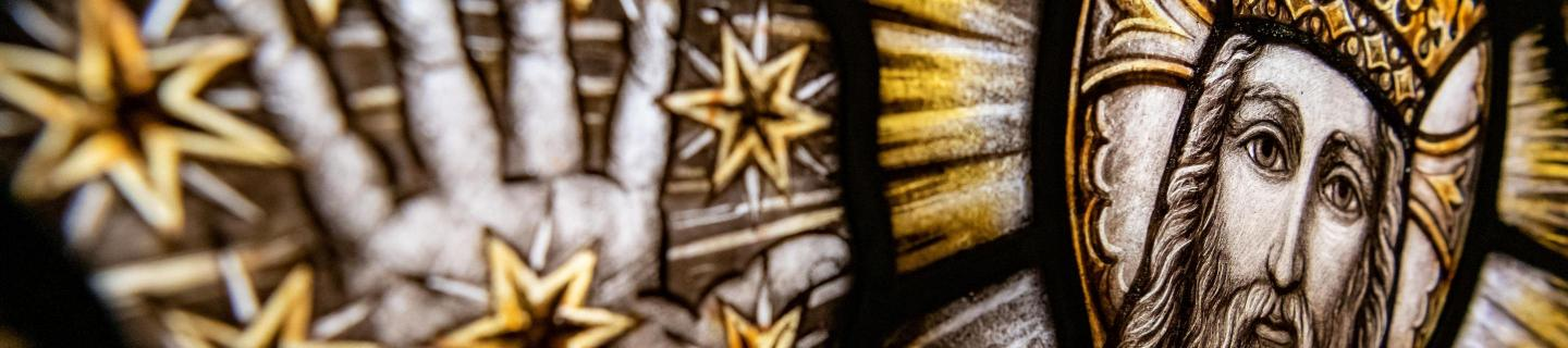 A close up shot of a stained window glass featuring a crowned man with a halo reading his arm out. His hand is surrounded by stars.